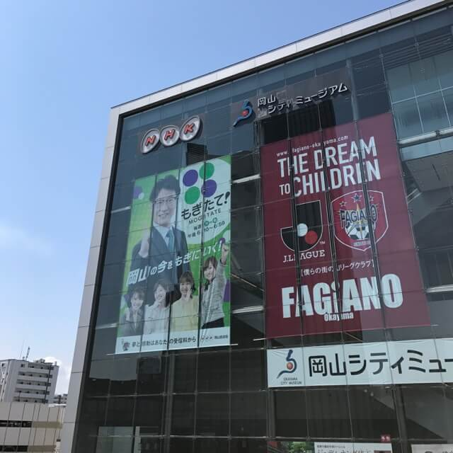 青空に映えるファジアーノ懸垂幕@岡山駅西口